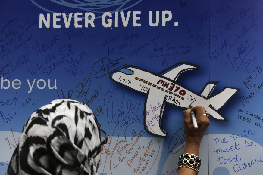 epa05197357 A woman writes messages for the passengers of missing Malaysia Airlines flight MH370 on a banner during a remembrance ceremony to mark the second anniversary of the plane's disappearance, in Kuala Lumpur, Malaysia, 06 March 2016. Malaysia Airlines flight MH370 disappeared on 08 March 2014, after changing course in a 'deliberate action', according to experts, only forty minutes after taking off from Kuala Lumpur en route to Beijing with 239 people on board including the crew and passengers.  EPA/FAZRY ISMAIL