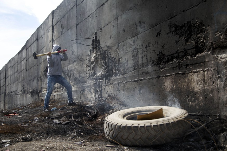A Palestinian student tries to break the separation barrier during clashes with Israeli troops, who were on the other side of the wall, following a protest near the Al-Quds University in the West Bank village of Abu Dis, near Jerusalem, Wednesday, Oct. 28, 2015. (AP Photo/Majdi Mohammed)