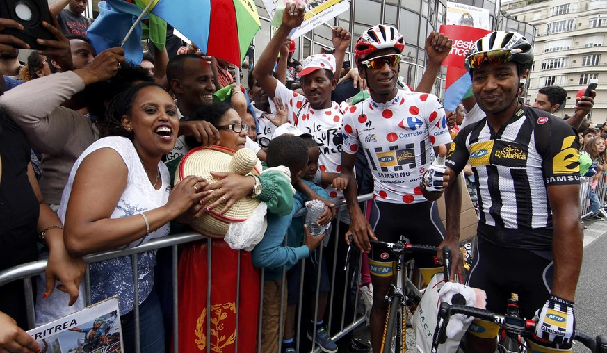 MTN-Qhubeka rider Daniel Teklehaimanot of Eritrea (C), best climber's dotted jersey, and team-mate Merhawi Kudus Ghebremedhin (R) pose with Eritrean supporters before the start of the 181.5-km (112.7 miles) 8th stage of the 102nd Tour de France cycling race from Rennes to Mur-de-Bretagne, France, July 11, 2015. REUTERS/Benoit Tessier