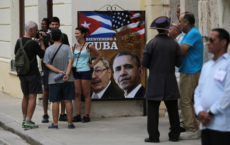 Tourists stand next to a sign showing President Barack Obama, right, and Cuba's President Raul Castro next to the Cathedral in Old Havana, Cuba, Sunday, March 20, 2016, ahead of Obama's arrival. In his historic visit to Cuba, Obama is relegating decades of American acrimony with the country further into the past and cementing a new relationship between the Cold War-era foes. (AP Photo/Enric Marti)