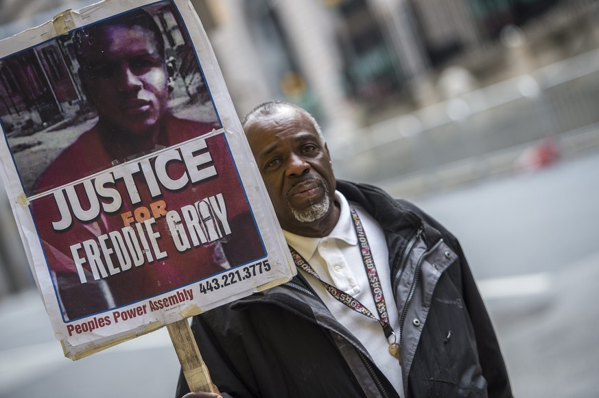 epa05071547 Protester Arthur Johnson Jr. carries a sign outside of the Baltimore City Circuit Court House East as the deadlocked jury continues to deliberate in the trial of Baltimore Police Officer William G. Porter in Baltimore, Maryland, USA, 16 December 2015. Officer Porter faces manslaughter and other charges in the April 2015 death of Freddie Gray.  EPA/SHAWN THEW