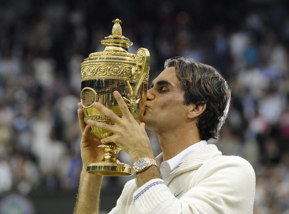 epa03300941 Roger Federer of Switzerland kisses the Championship trophy after defeating Andy Murray of Britain in the men's singles final of the Wimbledon Championships at the All England Lawn Tennis Club, in London, Britain, 08 July 2012.  EPA/GERRY PENNY