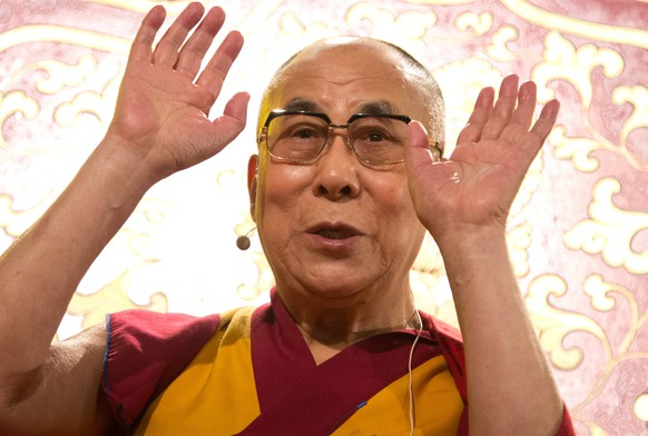 Tibetan spiritual leader Dalai Lama gestures during a ceremony in Hamburg, northern Germany, on August 26, 2014. With the Buddhist initiation, the Dalai Lama ended the spiritual part of his visit to the Hanseatic city. AFP PHOTO / DPA / CHRISTIAN CHARISIUS +++ GERMANY OUT