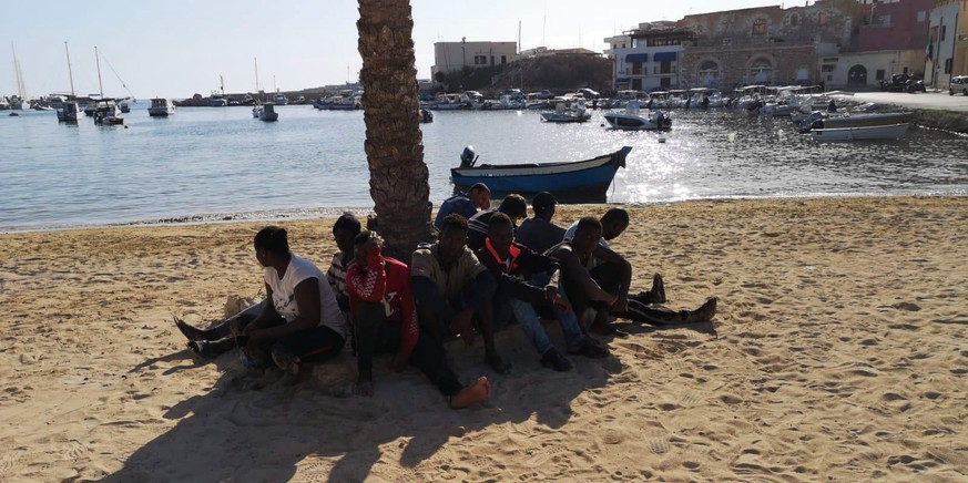 epa08564724 A group of sub-Saharan migrants sit around a tree at the beach after arriving in Lampedusa, southern Italy, 24 July 2020. The group crossed the Mediterranean in a small boat from Tunisian waters.  EPA/CONCETTA RIZZO