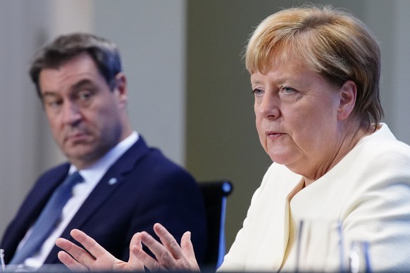epa08706231 German Chancellor Angela Merkel (R) gestures next to State Premier of Bavaria Markus Soeder (L) during a press conference after the meeting of German Federal State Premiers at the Chancellery in Berlin, Germany, 29 September 2020. The German Prime Ministerial Conference took place earlier in the day in Berlin to discuss the current coronavirus situation and possible change of measures.  EPA/CLEMENS BILAN / POOL