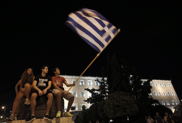 epa04832875 Supporters of the 'No' campaign wave flags and react after the first results of the referendum at Syntagma Square, in Athens, Greece, 05 July 2015. Greek voters in the referendum were asked whether the country should accept reform proposals made by its creditors.  EPA/YANNIS KOLESIDIS
