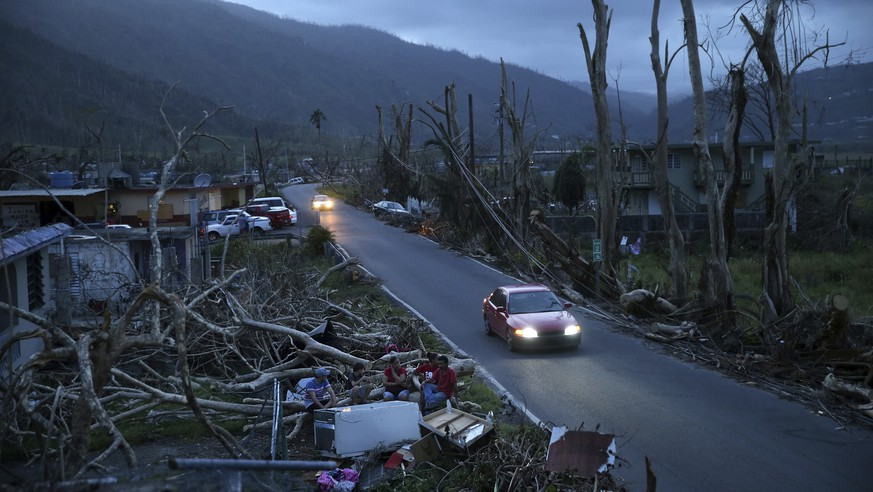 FILE - In this Sept. 26, 2017 file photo, neighbors sit on a couch outside their destroyed homes as the sun sets in the aftermath of Hurricane Maria, in Yabucoa, Puerto Rico. The strongest hurricane to ever hit Puerto Rico in nearly a century, officials predicted before Maria made landfall that it would decimate the power company's crumbling infrastructure and force the government to rebuild dozens of communities. (AP Photo/Gerald Herbert, File)