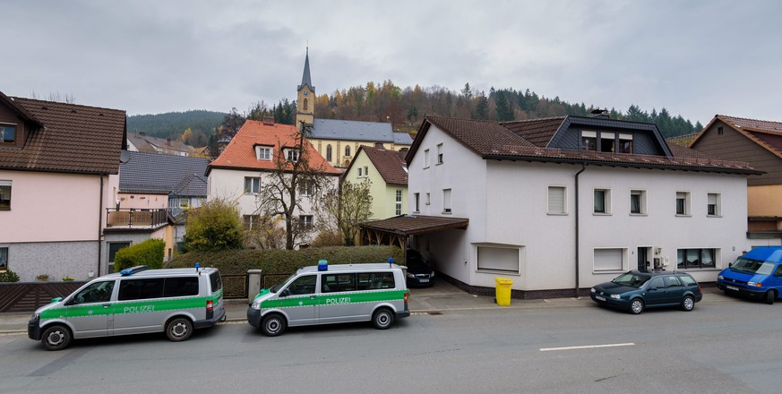 epa05023150 Police vehicles are parked near a residential building (R) in Wallenfels, Germany, 13 November 2015. The bodies of seven babies have been found at a home in the small German town, triggering a major police inquiry 13 November as investigators seek a 45-year-old woman for questioning. The bodies were found 12 November afternoon in a state of advanced decay. Pathologists are still to establish the infants' sexes and would look for more children among the remains.  EPA/NICOLAS ARMER