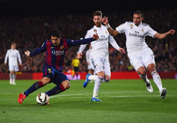 BARCELONA, SPAIN - MARCH 22:  Luis Suarez of Barcelona shoots past Sergio Ramos and Pepe of Real Madrid CF to score their second goal during the La Liga match between FC Barcelona and Real Madrid CF at Camp Nou on March 22, 2015 in Barcelona, Spain.  (Photo by David Ramos/Getty Images)