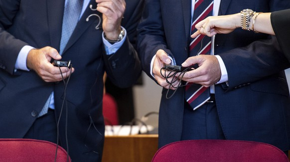 In one of Germany's biggest tax fraud trial, two British investment bankers stand in the courtroom in Bonn, Germany, accused of helping dubious transactions with massive tax losses for the state of around 440 million Euro, on Wednesday, Sept. 4, 2019. (Marius Becker/dpa via AP)