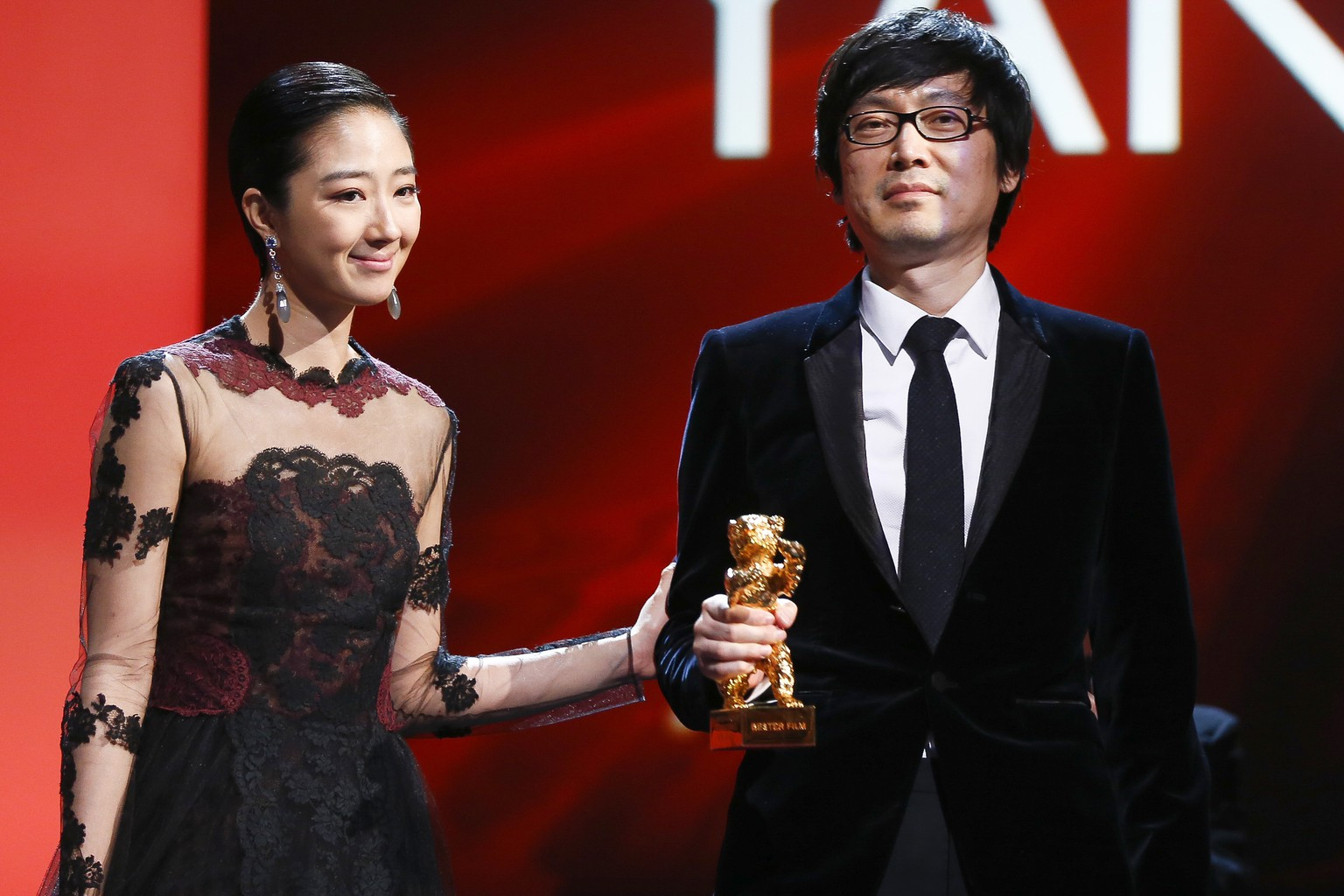 Director Diao Yina, right, holds the Golden Bear for Best Film for the movie Black Coal, Thin Ice, as he stands with actress Gwei Lun Meiduring during the award ceremony at the International Film Festival Berlinale in Berlin, Saturday, Feb. 15, 2014.  (AP Photo/Axel Schmidt)