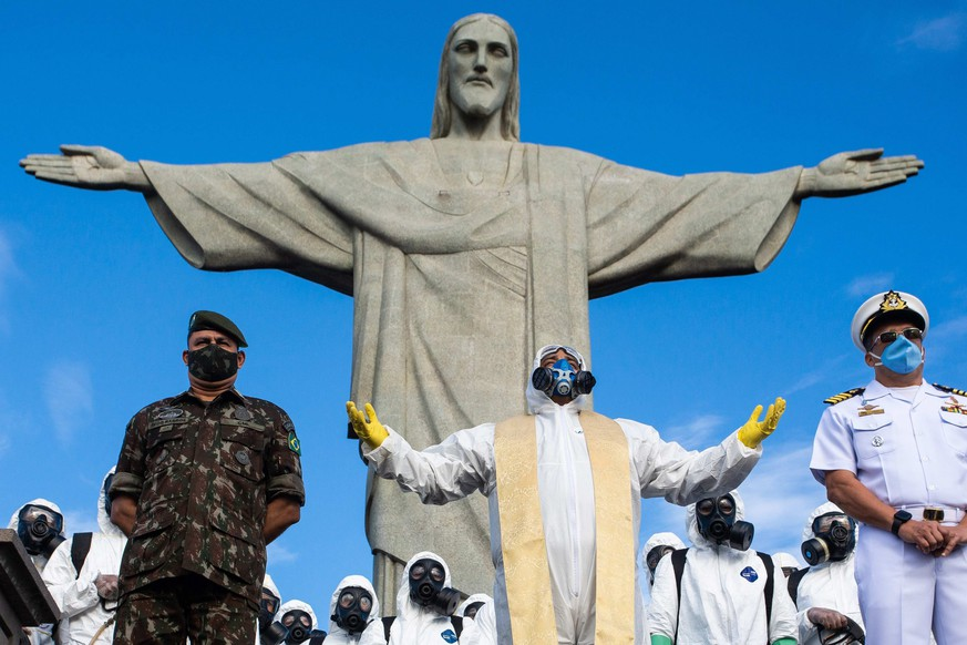 epa08601144 Reverend Omar (C) leads a short ceremony before soldiers of the Brazilian army disinfect the Cristo Redentor monument to reopen the tourist spot, in Rio de Janeiro, Brazil, 13 August 2020. The Christ of Corcovado, the most iconic image of Brazil in the world, will reopen its doors to the public on 15 August, as well as the P?£o de A?ß??car hill, the aquarium and the giant wheel, other of the main tourist attractions of Rio de Janeiro, after five months of inactivity due to COVID-19.  EPA/FERNANDO MAIA