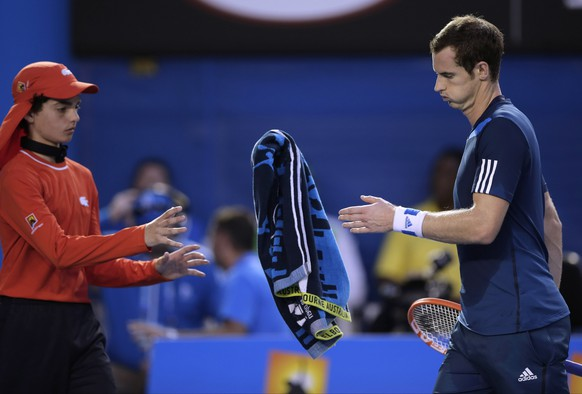 Andy Murray of Britain, right,  throws a towel to a ball boy as he plays Roger Federer of Switzerland in their quarterfinal at the Australian Open tennis championship in Melbourne, Australia, Wednesday, Jan. 22, 2014.(AP Photo/Rick Rycroft)