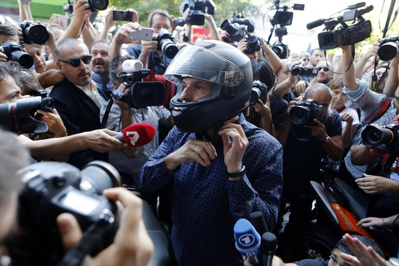 Outgoing Greek Finance Minister Yanis Varoufakis puts his helmet on as he is surrounded by media after his resignation in Athens, Monday, July 6, 2015. Greece and its membership in Europe's joint currency faced an uncertain future Monday, with the country under pressure to reach a bailout deal with creditors as soon as possible after Greeks resoundingly rejected the notion of more austerity in exchange for aid. (AP Photo/Petros Karadjias)