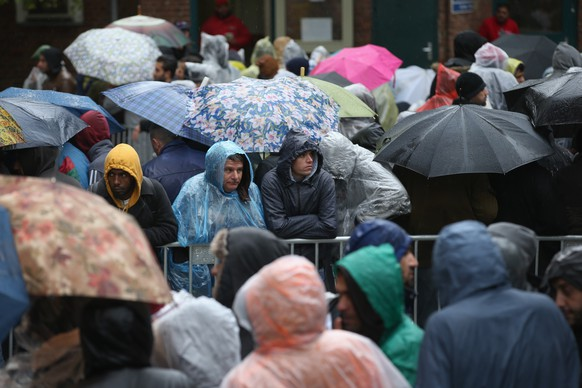 BERLIN, GERMANY - OCTOBER 08:  Migrants wait under rain and cold weather outside the Central Registration Office for Asylum Seekers (Zentrale Aufnahmestelle fuer Asylbewerber, or ZAA) of the State Office for Health and Social Services (Landesamt fuer Gesundheit und Soziales, or LAGeSo) on October 8, 2015 in Berlin, Germany. Migrants receive benefits, including housing vouchers and cash, at LAGeSo, and the office is currently so overwhelmed with the volume of applicants that migrants are waiting days on end to be admitted to the building. Germany is continuing to receive migrants, many of whom will apply for asylum, at a rate of several thousand per day. German Chancellor Angela Merkel, who has stated she is determined to keep Germany's borders open, is coming under increasing pressure from critics claiming Germany cannot cope with so many newcomers.  (Photo by Sean Gallup/Getty Images) *** BESTPIX ***