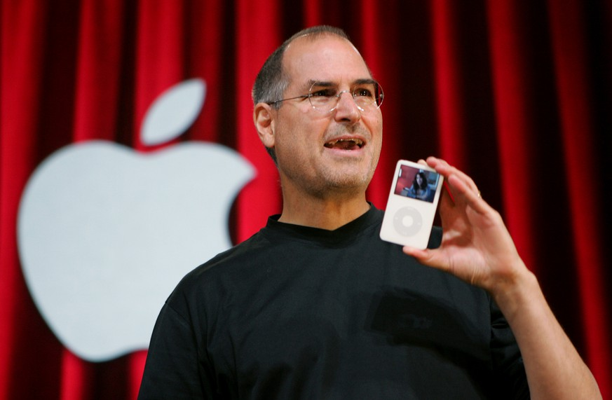 FILE - In this Oct. 12, 2005 file photo, Apple Computer Inc. CEO Steve Jobs holds up an iPod during an event in San Jose, Calif. Jurors in a class-action lawsuit against Apple Inc. on Tuesday, Dec. 2, 2014 saw emails from the late CEO and his top lieutenants that show Jobs was determined to keep Apple's popular iPod music players free from songs that were sold by competing online stores. (AP Photo/Paul Sakuma, File)