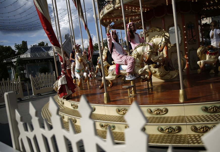 Girls in costumes ride a carousel near Red Square during the 2018 soccer World Cup in central Moscow, Russia, Friday, July 13, 2018. (AP Photo/Rebecca Blackwell)