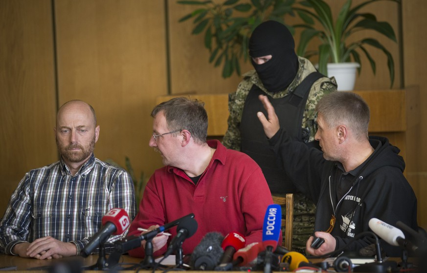 Vacheslav Ponomarev, the self-proclaimed mayor of Slovyansk, right, speaks to a pro-Russian gunman, as two of foreign military observer, one of them Axel Schneider of Germany, center, look to each other during a press conference in city hall, of Slovyansk, eastern Ukraine, Sunday, April 27, 2014. As Western governments vowed to impose more sanctions against Russia and its supporters in eastern Ukraine, a group of foreign military observers remained in captivity Saturday accused of being NATO spies by a pro-Russian insurgency. The German-led, eight-member team was traveling under the auspices of the Organization of Security and Cooperation in Europe when they were detained Friday. (AP Photo/Alexander Zemlianichenko)