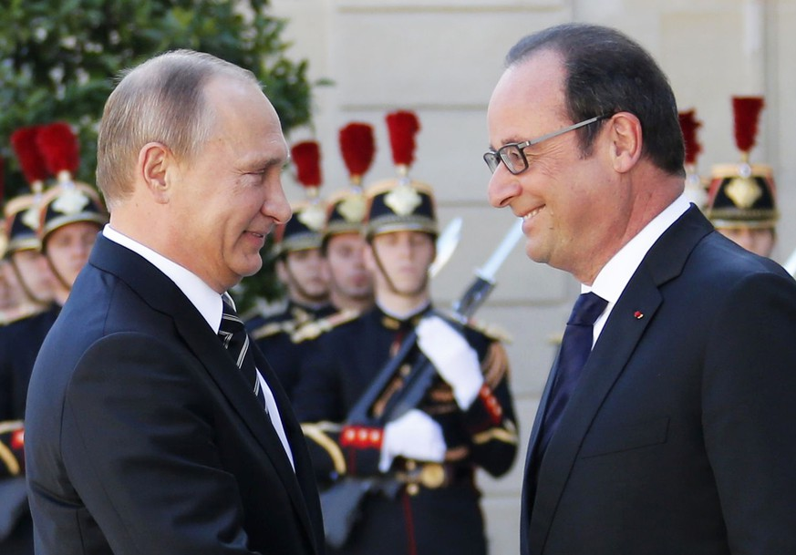French President Francois Hollande (R) welcomes Russia's President Vladimir Putin as he arrives attend a summit to discuss the conflict in Ukraine at the Elysee Palace in Paris, France, October 2, 2015. France hosts a meeting with leaders of Russia, Germany and Ukraine in Paris for talks about Ukraine which were likely to be overshadowed by the conflict in Syria.  REUTERS/Regis Duvignau