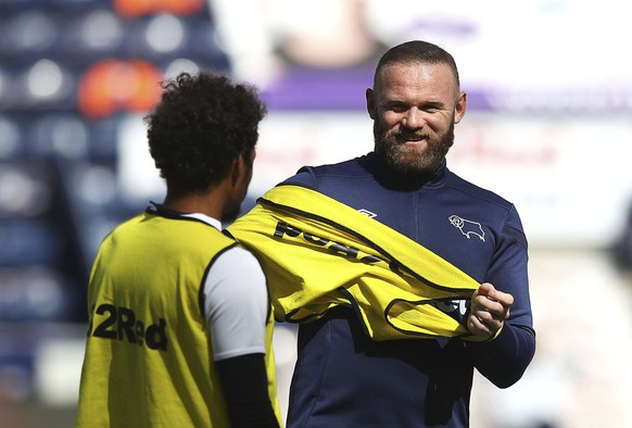 Derby County's Duane Holmes, left, and Wayne Rooney warm up before their English Championship soccer match against Preston North End at Deepdale, Preston, England, Wednesday, July 1, 2020. (Martin Ricket/PA via AP)
