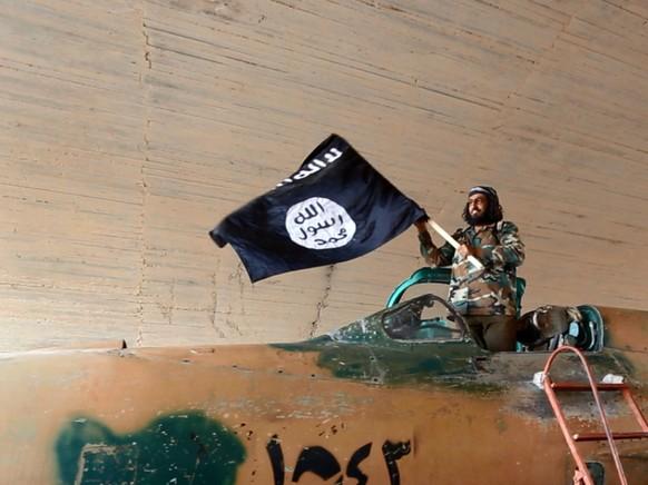 Ein Kämpfer der Terrormiliz Islamischer Staat (IS) mit einer Flagge. (Symbolbild)