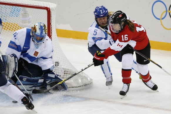 Goalkeeper Noora Raty of Finland blocks Jayna Hefford's of Canada (16)shot at the goal as Anna Kilponen of Finland (5) closes in during the third period of the 2014 Winter Olympics women's ice hockey game at Shayba Arena, Monday, Feb. 10, 2014, in Sochi, Russia. (AP Photo/Petr David Josek)