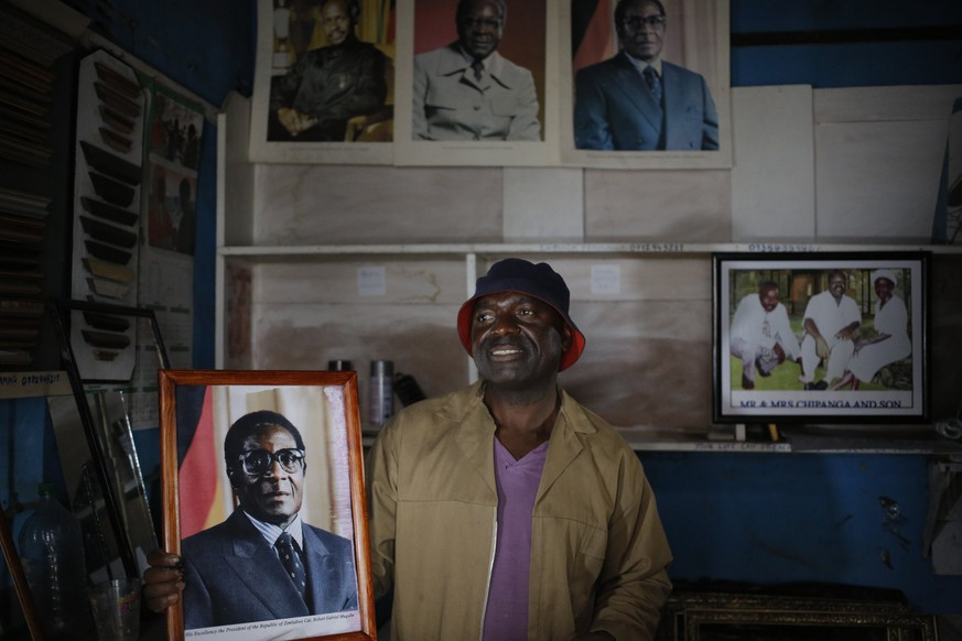epa06335257 Picture framer, Freddy Chitanda (48) holds a framed portrait of President Robert Mugabe at his small street side picture framing shop in Harare, Zimbabwe, 17 November 2017.  The shop has not lights as there is no power after electricity cuts became common recently. He has framed many portraits of President Mugabe for local offices and government institutions. This comes days after a military take over that included placing President Robert Mugabe under house arrest. Zimbabwe has a 95% unemployment rate with the country experiencing hyper inflation resulting in the country suspending its own currency.  EPA/KIM LUDBROOK