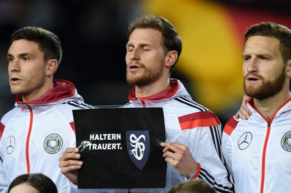 KAISERSLAUTERN, GERMANY - MARCH 25:  Benedikt Hoewedes of Germany holds up a banner in remembrance of the victims of Germanwings flight 4U9525 prior to kickoff during the International Friendly match between Germany and Australia at Fritz-Walter-Stadion on March 25, 2015 in Kaiserslautern, Germany. The Germanwings flight 4U9525 crashed in the French Alps on March 24, 2015 at Seyne, France. The Airbus A320 airliner travelling from Barcelona to Dusseldorf went down with 150 people onboard.  (Photo by Matthias Hangst/Bongarts/Getty Images)