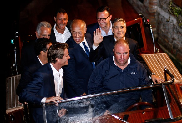 George Clooney (2nd row R) waves to his fans waves as he leaves the restaurant Da Ivo with friends and his father during his stag night event in Venice on September 27, 2014. Clooney and his Lebanon-born British fiancee Amal Alamuddin arrived in Venice on September 26 for a spectacular waterfront wedding billed as the party of the year. AFP PHOTO / PIERRE TEYSSOT