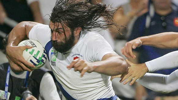 Sebastien Chabal of France, left, charges through to score a try during the Rugby World Cup Group D match between France and Namibia, Toulouse, southwestern France, Sunday Sept. 16, 2007.  (AP Photo/Katsumi Kasahara)
