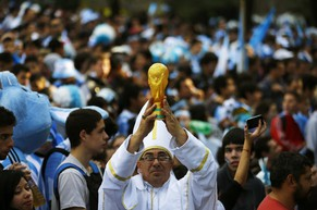 A soccer fan dressed up as Pope Francis holds up a replica of the World Cup trophy, before the World Cup final soccer match between Argentina and Germany, in Buenos Aires July 13, 2014. REUTERS/Ivan Alvarado (ARGENTINA - Tags: SPORT SOCCER WORLD CUP RELIGION TPX IMAGES OF THE DAY)