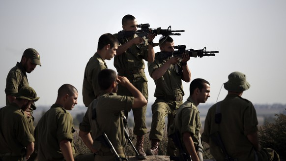 Israeli soldiers from a paratrooper brigade looks through their gun scopes towards Gaza city before beginning training exercises near the Israel Gaza border, Monday Sept. 22, 2013. Egypt will host a brief round of indirect talks this week between Israelis and Palestinians on a sustained Gaza cease-fire deal, as well as negotiations between Palestinian rivals Hamas and Fatah on who should run the territory, a Palestinian official said Sunday. (AP Photo/Tsafrir Abayov)