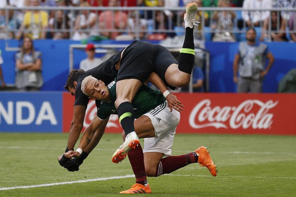 Mexico's Javier Hernandez, bottom, crashes with Brazil goalkeeper Alisson during the round of 16 match between Brazil and Mexico at the 2018 soccer World Cup in the Samara Arena, in Samara, Russia, Monday, July 2, 2018. (AP Photo/Frank Augstein)
