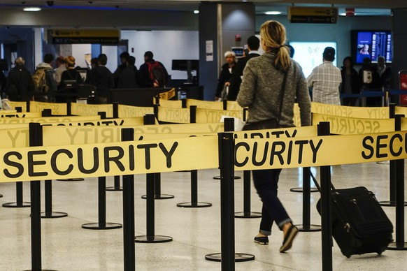 Passengers make their way through a security checkpoint at JFK International Airport in New York in this file photo taken October 11, 2014. Travelers entering the United States whose trips originated in Ebola-stricken Liberia, Sierra Leone or Guinea must fly into one of five airports that have enhanced screening in place, the U.S. Department of Homeland Security said on Tuesday.  REUTERS/Eduardo Munoz/Files   (UNITED STATES - Tags: TRANSPORT HEALTH TRAVEL)