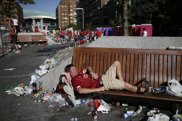 A Liverpool supporter sleeps on a bench at the fan zone in downtown Madrid prior to the Champions League final soccer match between Tottenham Hotspur and Liverpool at the Wanda Metropolitano Stadium in Madrid, Saturday, June 1, 2019. (AP Photo/Andrea Comas)