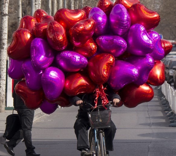epa03105175 A cyclist transports heart shaped balloons for sale to those marking Valentines Day in Beijing, China 14 February 2012. Although China has its own traditional festival celebrating lovers the commercial drive behind the western style of celebrating St Valentine's Day has found many willing followers especially in the larger cities.  EPA/ADRIAN BRADSHAW