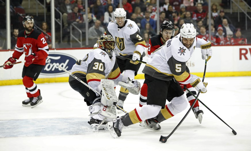 Vegas Golden Knights defenseman Deryk Engelland (5) tries to corral the puck away from New Jersey Devils center Nico Hischier (13) in front of Golden Knights goaltender Malcolm Subban (30) during the second period of an NHL hockey game, Tuesday, Dec. 3, 2019, in Newark, N.J. (AP Photo/Kathy Willens) Deryk Engelland,Nico Hirschier,Malcolm Subban