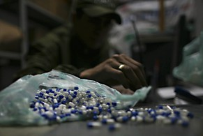 A police officer counts seized pills containing cocaine at a police station after a routine anti-drug operation in Ciudad Bolivar, south of Bogota, Thursday, Nov. 26, 2009. (AP Photo/William Fernando Martinez)