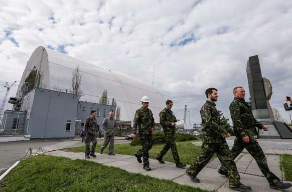 epa05265651 Workers walk next to the construction of a new protective shelter which will be placed over the remains of the nuclear reactor Unit 4, at Chernobyl nuclear power plant, in Chernobyl, Ukraine, 16 April 2016 (issued 18 April). Construction works for a new protective shelter which will be mounted over the old one are currently underway at the site near. The explosion of Unit 4 of the Chernobyl nuclear power plant in the early hours of 26 April 1986 is still regarded the biggest accident in the history of nuclear power generation. Ukrainians will mark the 30 anniversary of Chernobyl's tragedy annually on 26 April 2016.  EPA/ROMAN PILIPEY