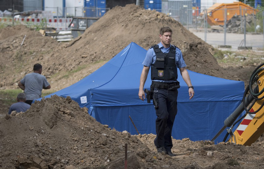 In this photo taken Wednesday, Aug. 30, 2017 in Frankfurt, Germany, a police officer passes a blue tent that was set up over a 1.8 -ton bomb of a type dropped by British bombers during World War II. City authorities in Frankfurt plan to evacuate more than 60,000 people from their homes on Sunday to defuse the bomb found during construction work this week. (Boris Roessler/dpa via AP)