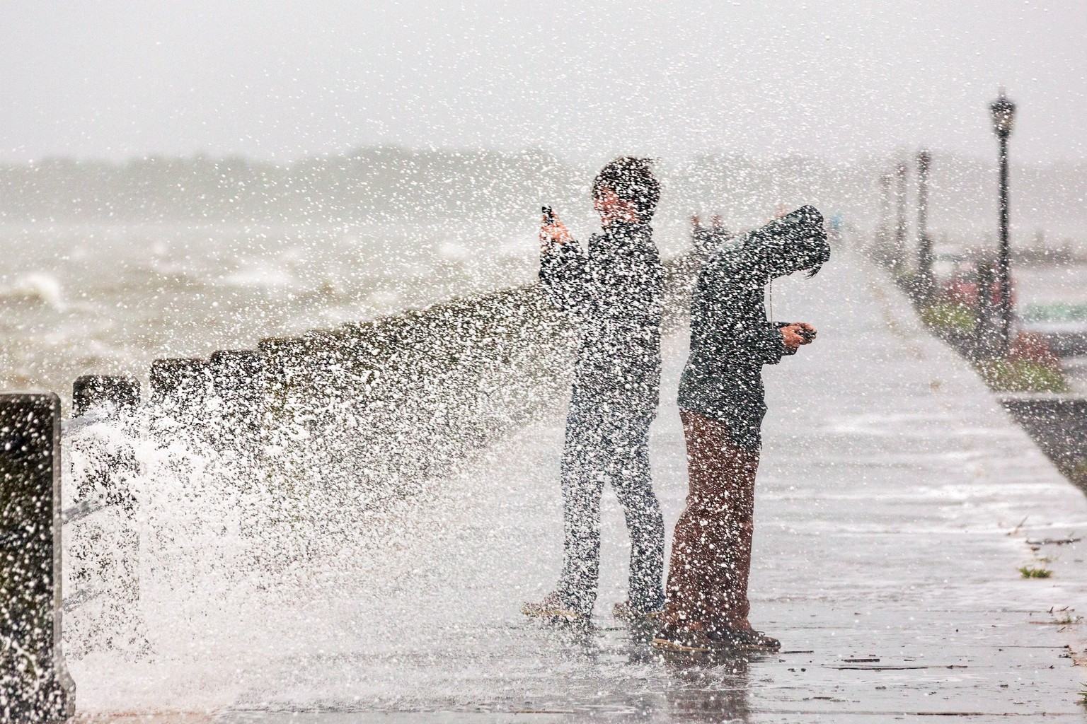 epa04962239 A group of tourists take photos as massive waves splash over the historic Battery as Hurricane Joaquin brings heavy rain, flooding and strong winds as it passes offshore in Charleston, SC, USA, 03 October 2015. Flood warnings and watches were posted in several eastern US states where more heavy rainfall was forecast to reach accumulations of up to 25 centimetres in already saturated areas. Hurricane Joaquin, which has moved to the west of Bermuda over open ocean, is partially to blame for the rainfall, the weather service said. But the storm is expected to turn toward the north-northeast on Sunday and not ram the east coast of the United States.  EPA/RICHARD ELLIS