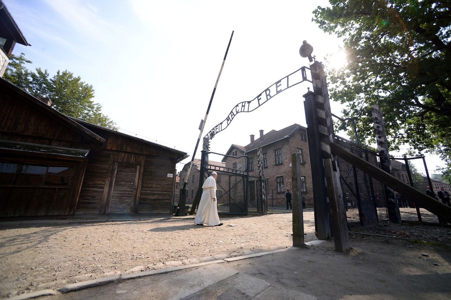 Pope Francis walks through Auschwitz's notorious gate with the sign