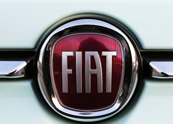FILE - In this Oct. 31, 2019 file photo, a Fiat logo is pictured on a car in Bayonne, southwestern France. Fiat Chrysler Automobiles and PSA Peugeot announced Wednesday, Dec. 18, 2019, that their boards signed a binding deal to merge the two automakers, creating the world's fourth-largest auto company. (AP Photo/Bob Edme, File)