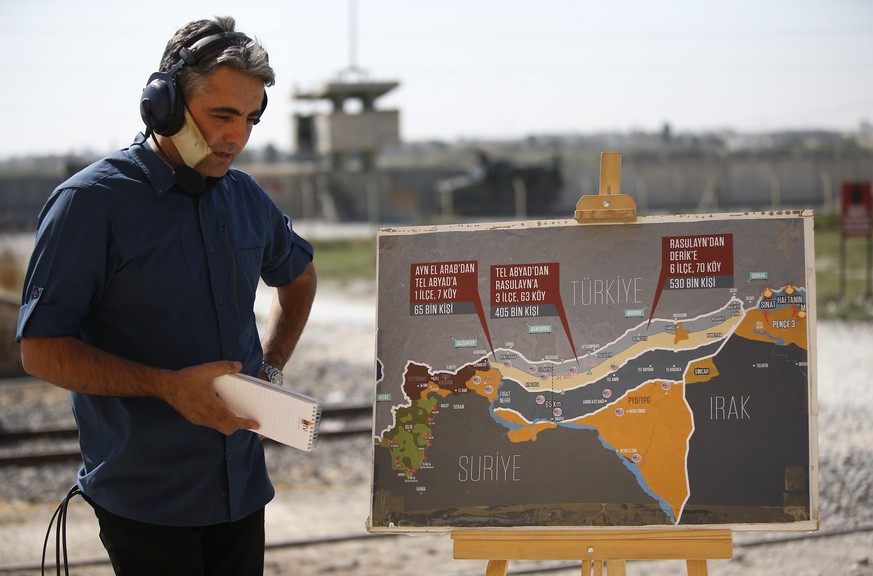 A TV journalist prepares to work in front of a map showing Turkey's suggested operation in Syria, at the border between Turkey and Syria, in Akcakale, Sanliurfa province, southeastern Turkey, Tuesday, Oct. 8, 2019. Turkey's vice president Fuat Oktay says his country won't bow to threats in an apparent response to U.S. President Donald Trump's warning to Ankara about the scope of its planned military incursion into Syria. (AP Photo/Lefteris Pitarakis)