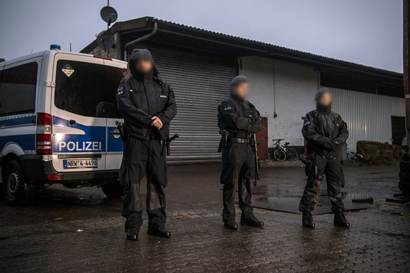 epa05631905 Police officers stand guard in front of a warehouse during a search in Pulheim, Germany, 15 November 2016. Several police officers took part in an anti-terrorism raid against suspected supporters of the Islamic State (IS or ISIS) militant group. Authorities held raids against Islamist networks in ten German states.  EPA/WOLFRAM KASTL ATTENTION EDITORS: FACES PIXELATED AT SOURCE