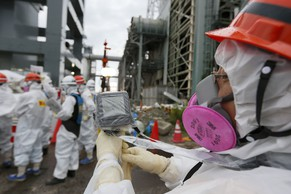 A Tokyo Electric Power Co. (Tepco) employee measures radiation levels as workers conduct operations to construct an underground ice wall at Tepco's tsunami-crippled Fukushima Daiichi nuclear power plant in Fukushima Prefecture July 9, 2014. The media were shown on Tuesday the site where Tepco is building a massive underground ice wall to contain leaking radioactive water. The utility is planning to build a 1.4-kilometre underground wall of ice around four reactor buildings at Fukushima to prevent underground water from flowing in, and stop radioactive water seeping into the Pacific Ocean. In the three years since a massive earthquake and tsunami set off nuclear meltdowns at Fukushima, Tepco has been fighting a constant battle to pump out, treat and store hundreds of thousands of tonnes of contaminated water. REUTERS/Kimimasa Mayama/Pool (JAPAN - Tags: BUSINESS CONSTRUCTION DISASTER ENERGY ENVIRONMENT)