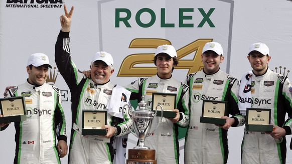 GT Daytona class winners in the IMSA 24-hour auto race, from left to right, Daniel Morad, Carlos de Quesada, Michael Christensen, of Denmark, Jesse Lazare and Michael de Quesada, display their Rolex watches at Daytona International Speedway, Sunday, Jan. 29, 2017, in Daytona Beach, Fla. (AP Photo/John Raoux)