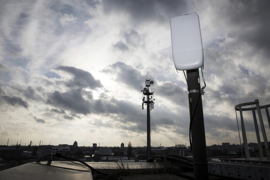 An antenna for the next 5G mobile internet standard is tested on a house in Hamburg, Germany, Thursday, Feb. 7, 2019. Germany want to sell frequencies for the next mobile generation by auction this year. (Christian Charisius/dpa via AP)