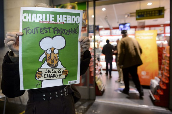 epa04560499 People shows the front page of French satirical magazine Charlie Hebdo in front of a news stand in Lausanne, Switzerland, early 15, January 2015. In an emotional act of defiance, Charlie Hebdo resurrected its irreverent and often provocative newspaper, featuring a caricature of the Prophet Muhammad on the cover that drew immediate criticism and threats of more violence after the 07 January Islamist attacks in Paris.  EPA/LAURENT GILLIERON