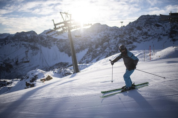 epaselect epa08850317 A Ski enthusiasts with protective face mask enjoys the day in Arosa, Switzerland, 29 November 2020. Ski resorts in Switzerland are open despite the Covid-19 coronavirus pandemic with strict safety measures.  EPA/GIAN EHRENZELLER
